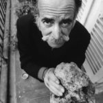 William Saroyan standing on his balcony holding a piece of rock from Armenia.
